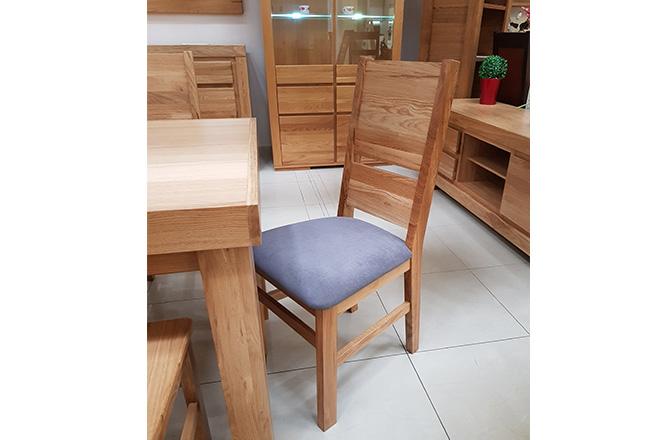 Krzesło dębowe Eryk B z tapicerką. Wybarwienie naturalne(lakier). Naturalne wybarwienie dębu zabezpieczone lakierem. W obiciu wykorzystano tkaninę łatwo-czyszczącą w niebieskiej kolorystyce.
